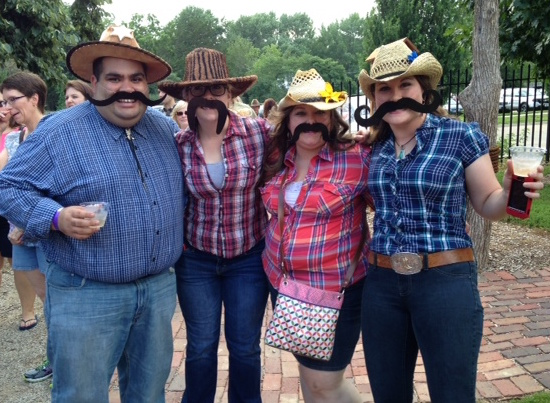 four people wearing fake mustaches at an outdoor event